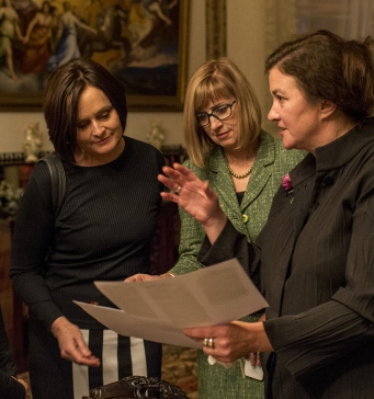 Three women stand in a beautifully furnished drawing room talking to a museum curator