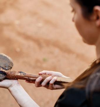 Student holding stone axe