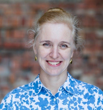 Portrait of woman in blue and white patterned shirt standing against brick wall.