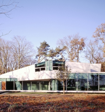 White house with many glass paneled walls across the front, set amongst Autumn leaves and trees