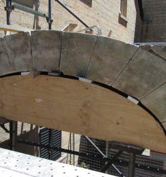Stone arch supported by piece of shaped wood.