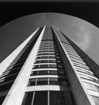 Looking up at top of circular building. Black & White photo.