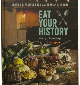 Cover of Eat your history cook book. Picture of food on a table with fire in the background.