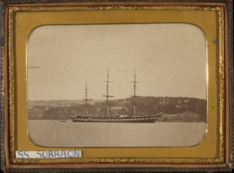 This is a sepia photograph of a three masted ship with sails furled sitting in a calm harbour