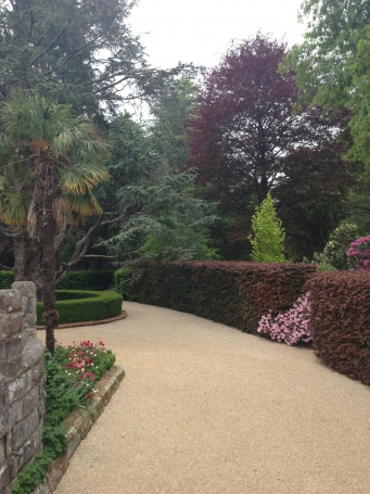 This is a photograph of a pathway with surrounding hedges and garden