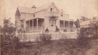 Sepia toned photograph of family group outside house.