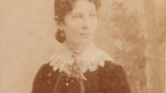 Formal portrait of woman wearing dark dress with white lacy collar and with dark hair bundled low on neck.