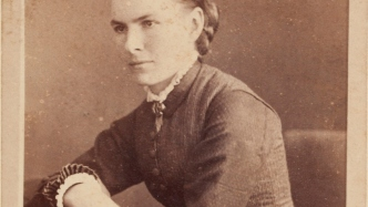 Portrait of woman in dark button front dress, leaning forward on lightly crossed arms.
