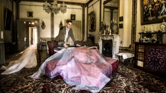 Man uncovering furniture which has been protected from dust