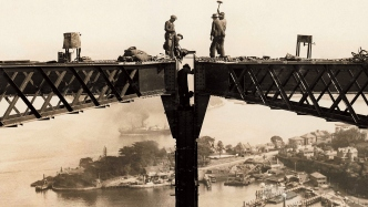 Image of a partly constructed bridge with workers standing on steel girders high above the harbour.