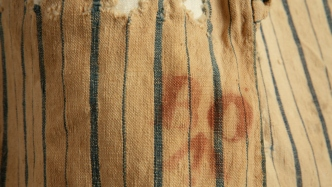 Closeup of broad arrow and B.O. [Board of Ordnance] stamps on striped fabric.