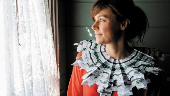 Dark haired woman wearing large ornate collar with red top, stares out of a curtained window