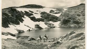Image of two people on horseback beside a lake