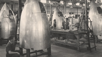 Black and white photo of men in missile factory