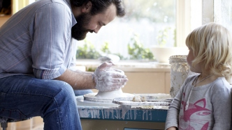 Man working on pottery wheel with small girl watching.
