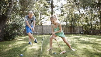 Two children with mallets playing croquet on a green lawn with fence in background