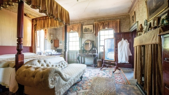 Ornately furnished bedroom with canopied bed and chaise longue to left and windows at rear.