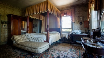 Large four poster bed with canopy in middle of room full of other furnishings, backlit by window.