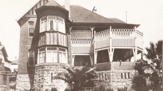 Black and white photo of two storey sandstone base house with verandahs.