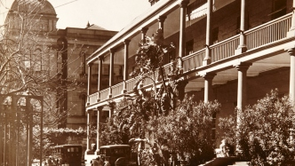 Large 2 storey building with deep verandahs, steps leading to lower verandah and bushes and driveway in the foreground.