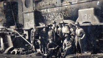 Close crop of photograph showing boys in group in front of train engine.