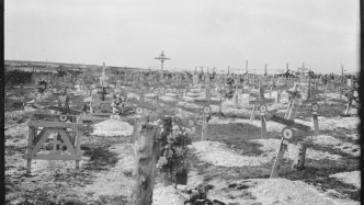 Stark black and white photo of barren grave yard.