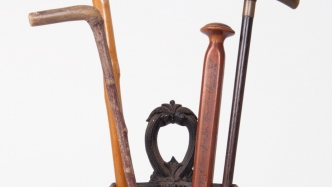 Deep-etched image of umbrella stand and four walking sticks on white background.