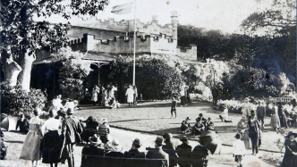 Black and white photograph of people seated and standing with house in background.