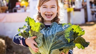 Smiling girl holding large cauliflower in outdoor setting.
