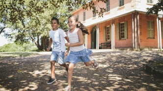 Two children running in garden in front of two storey farmstead building.