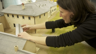 Woman leaning over scale model at work adjusting section of verandah roof.