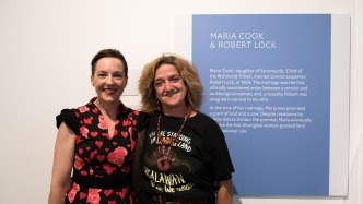 Two women in front of exhibition panel.
