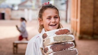 Girl dressed as convict carrying bricks.