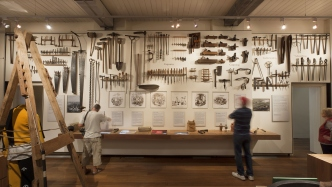A museum visitor looks at a large white wall featuring an elaborate and extensive arrangement of convict tools.