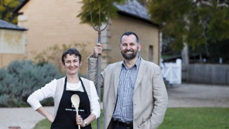 Two people in front of house holding objects.