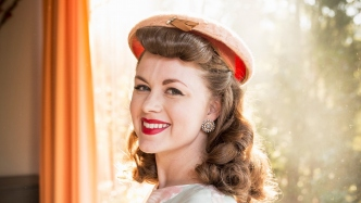 Young woman dressed up in Fifties attire stares at the camera