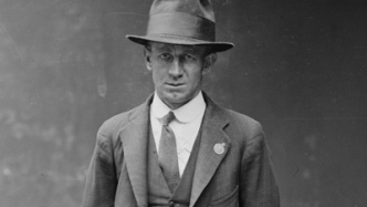 Black and white mugshot of man in suit and hat.