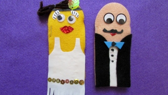 Two felt puppets, representing female and male getting married.