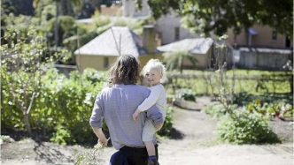 Man holding small child in garden facing away from camera with house in background.