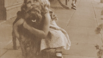 Sepia toned photo of young girl with dog.