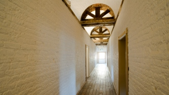 View along interior corridor towards sunlit window, with wooden ceiling arches visible.