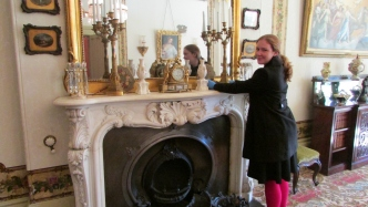 Person arranging objects on ornate mantelpiece.