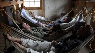 Reenactment of 5 convicts lying in hammocks
