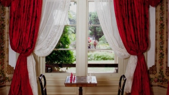 Closeup of curtains and small table with chairs
