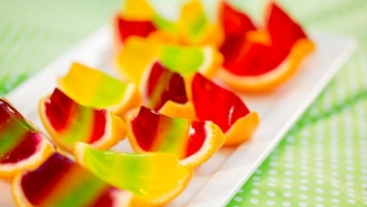 Sliced oranges filled with multicoloured layers of jelly.