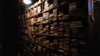 Interior shot of darkened room with shelving crammed with papers and files.