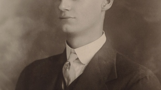 Black and white portrait photo of young man in suit.