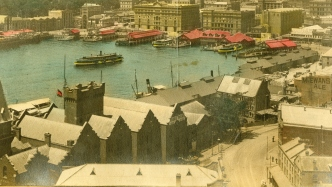 Hand coloured panoramic view from above of foreshores with ferries, quays and warehouses.