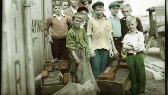 Colourised image of boys standing around with wheel borrows filled with bricks.