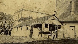 B/W photograph showing a wood panelled carpenter's workshop in the grounds of Australian Museum with stone walled octagonal cottage and stone walls of the main museum building on the right.